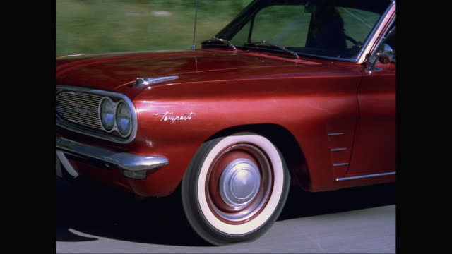 ms ts 1961s pontiac tempest car moving on road / united states - pontiac stock videos and b-roll footage