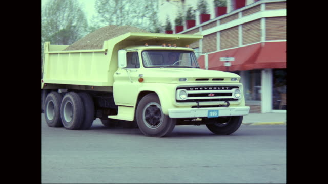 ws pan tu 1965s chevrolet dump truck moving on road, passes a chevy el camino pickup filled with standing cheerleaders cheering in the back / united states - chevrolet stock videos & royalty-free footage