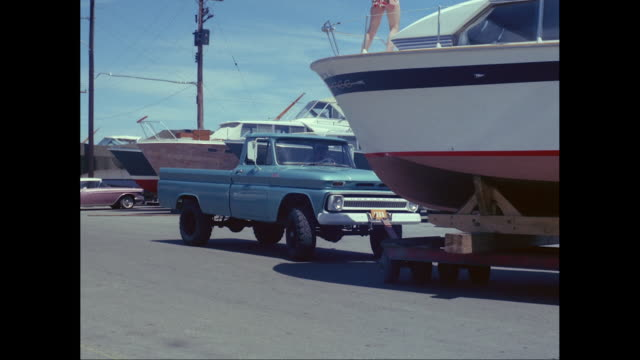 ws pan 1965s chevrolet pick-up pushing a yacht with two people on it strapped to a trailer / united states  - chevrolet stock videos & royalty-free footage