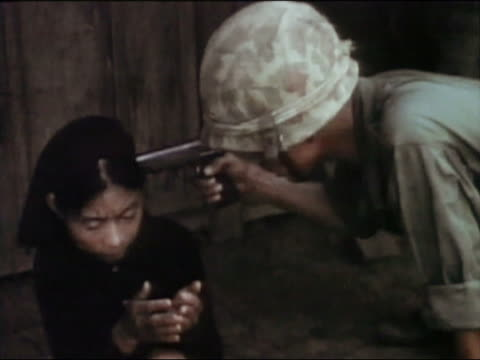 1967s medium shot us air force soldier questioning woman while shoving gun to her head / vietnam - threats stock videos and b-roll footage