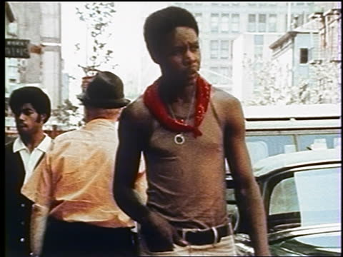 1970s Black man with bandanna around neck + pen in mouth walking on NYC street / documentary
