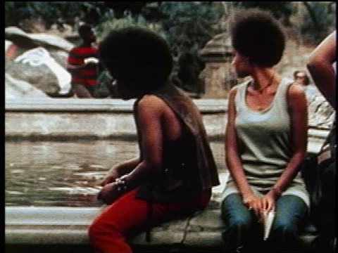 vídeos de stock e filmes b-roll de 1970s pan black people with afros sitting on edge of fountain / tilt down to feet / pan to group of hippies - afro americano