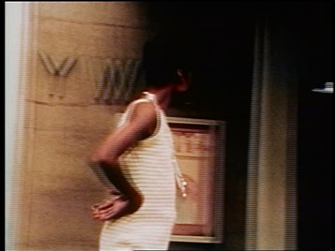 vídeos de stock, filmes e b-roll de 1970s black prostitute turning + walking in front of ywca on nyc sidewalk / documentary - prostituta