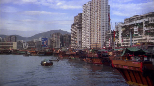 1970s boat point of view docks along river w/junk boats and buildings in background / Hong Kong
