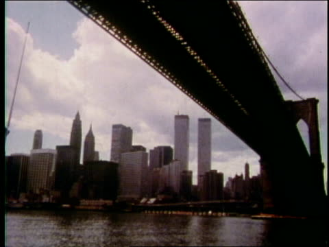 1970s boat pov under the brooklyn bridge, wtc towers & downtown manhattan skyline in background   - anno 1975 video stock e b–roll