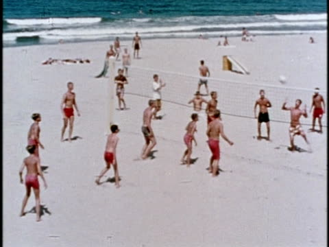 vídeos de stock, filmes e b-roll de 1970s ws boys playing volleyball on beach / los angeles, california - califórnia