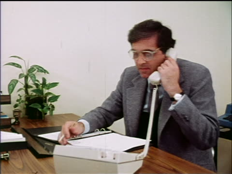 1970s businessman with binder on desk in front of him talking on telephone in office / industrial - nur männer über 40 stock-videos und b-roll-filmmaterial