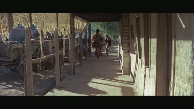 1970s ws cattle stampeding through porch, cowboys running away - solo uomini video stock e b–roll