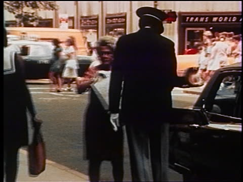 1970s chauffeur holding door + giving shopping bag to senior woman exiting limousine on NYC street