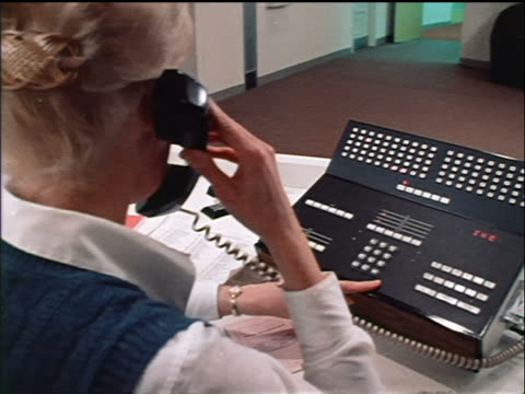 1970s close up dolly shot over-the-shoulder blonde woman at desk on multiple-line telephone in office / industrial - landline phone stock videos and b-roll footage