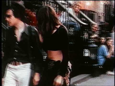 1970s couple walking on NYC street / woman wearing cropped shirt + sarong skirt / documentary