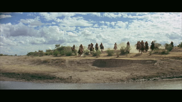 1970s WS Cowboys riding horses by river, one falling off horse