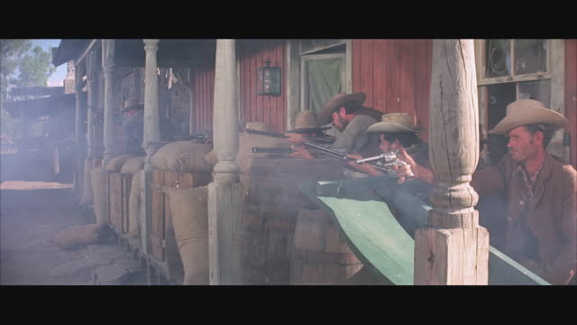 vidéos et rushes de 1970s ws cowboys shooting from behind barricade on porch - ouest américain