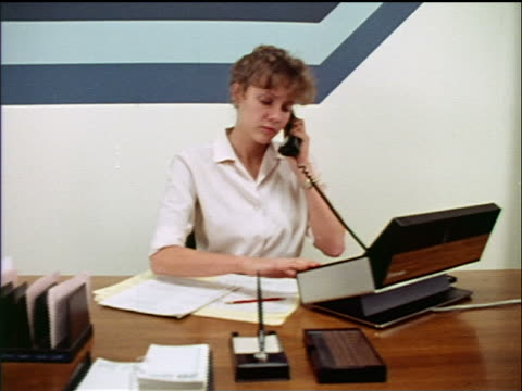 1970s dolly shot woman (receptionist) at desk using multiple-line telephone in office / industrial