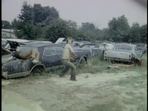 1970s film montage ws men fighting in junkyard/ ms man swinging mallet and breaking car windshield/ ws men fighting in puddle/ ms man pinning opponent on ground/ audio  - junkyard stock videos and b-roll footage