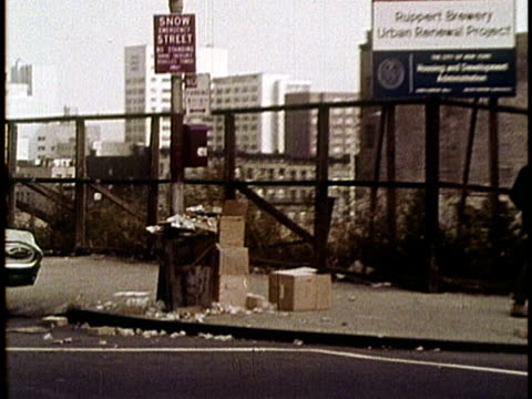 1970s FILM MONTAGE MS Woman in park/ WS ZO Empire State Building from trainyard/ MS Man walking past fence/ MS Truck exhaust/ MS Smokestack/ MS PAN Garbage on sidewalk/ WS Subway arriving/ New York, New York