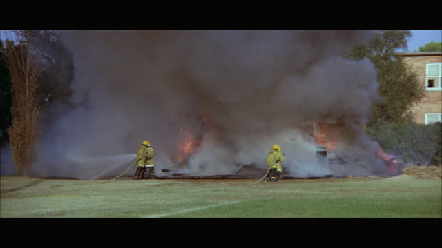 vídeos de stock e filmes b-roll de 1970s ws firemen fighting fire with hoses - 1970 1979