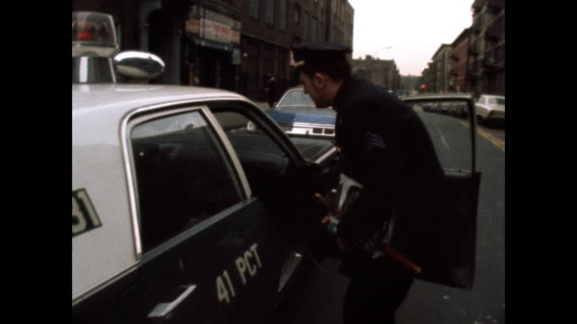 1970s following a police car as he goes to his police car in the bronx. - police car stock videos & royalty-free footage