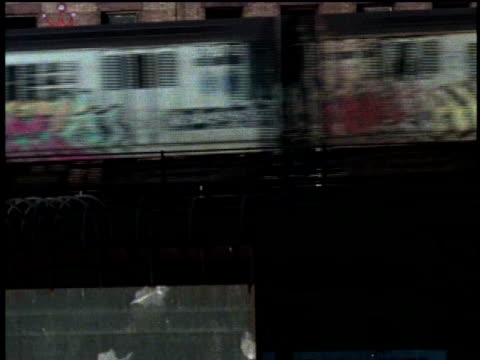 1970s ms pan graffiti-covered elevated subway train moving past apartment building in city / new york, new york, usa - bロール点の映像素材/bロール