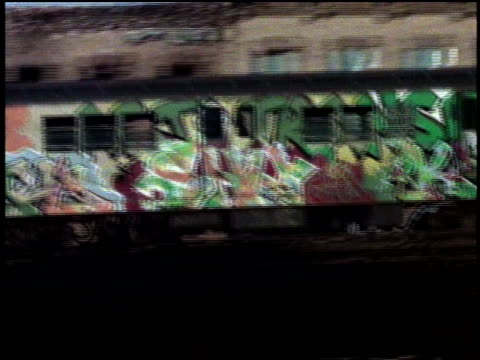 1970s ws pan graffiti-covered elevated subway train moving past apartment building in city / new york, new york, usa - bロール点の映像素材/bロール