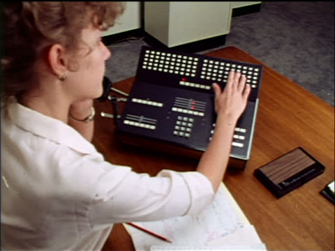 1970s high angle over-the-shoulder woman (receptionist) pushing buttons on multiple-line phone at desk in office