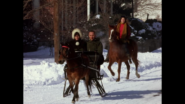 1970s Home Movie - Couple riding horse sled in snowed street