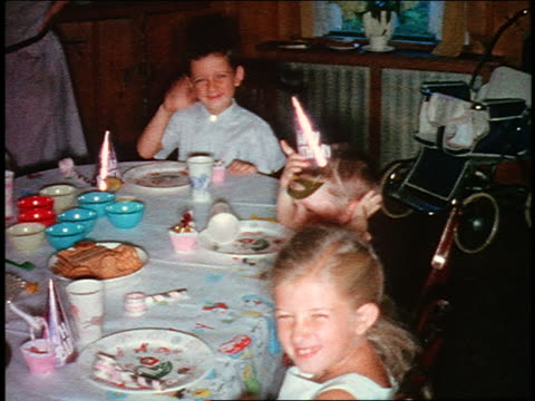 vidéos et rushes de 1970s home movie three children sitting at table waving to camera at birthday party - enfant d'âge scolaire