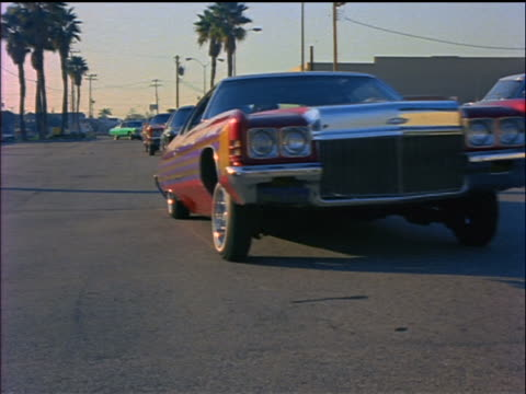 1970s line of low rider cars driving past camera on street / Los Angeles / educational