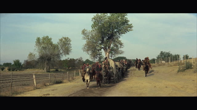 stockvideo's en b-roll-footage met 1970s ws line of wagons and horsemen - paardenkar