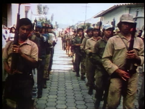 1970s lines of sandinista rebels carrying rifles marching on street past camera / nicaragua - nicaragua stock videos & royalty-free footage
