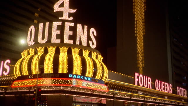 1970s long shot pan 'four queens' neon hotel sign to strip at night / las vegas - 1975 stock videos and b-roll footage