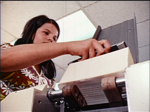 1970s low angle close up woman putting stack of punch cards into computer in office / educational - punch card stock videos & royalty-free footage