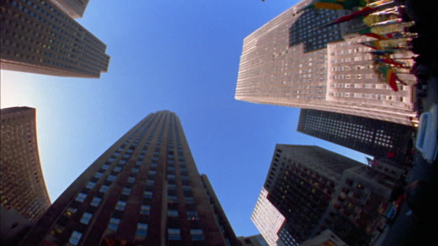 1970s low angle pan skyscapers and blue sky in rockefeller center / nyc - rockefeller center video stock e b–roll