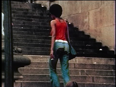 1970s low angle zoom out REAR VIEW Black woman wearing patched jeans + tank top walking up stairs / Central Park