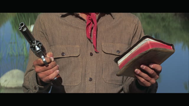 1970s cu man holding gun in one hand and bible in other - handgun stock videos & royalty-free footage