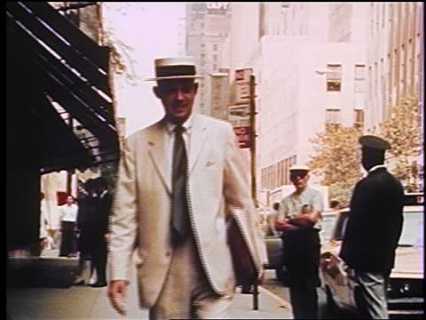1970s man wearing suit + boater walking on NYC sidewalk / documentary
