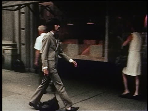 1970s pan man with mustache in suit carrying bag walking on sidewalk + entering store / nyc - anzug stock-videos und b-roll-filmmaterial