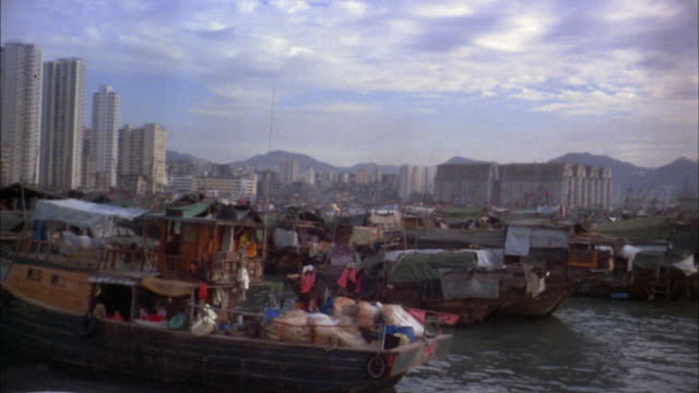 vídeos de stock e filmes b-roll de 1970s medium shot boat point of view past junk boats in river / hong kong - barco casa
