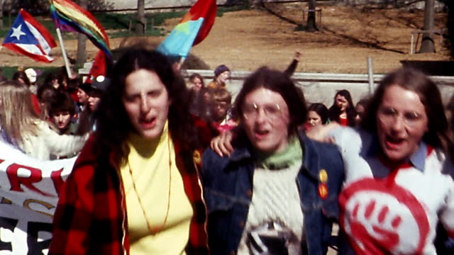 1970s medium shot group of young women walking toward CAM carrying banners during feminist march