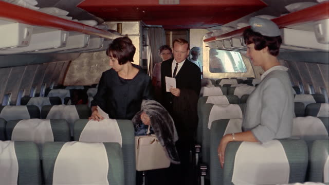 1970s medium shot passengers boarding airplane and taking their seats