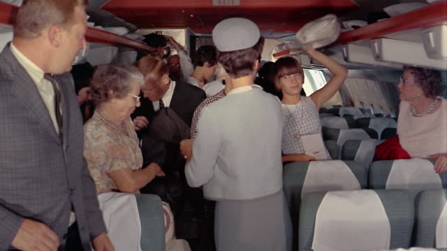 1970s medium shot passengers get up from seats and leave airplane