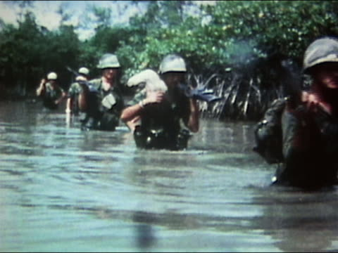 1970s medium shot soldiers wading though water carrying guns and supplies / vietnam / audio - vietnam war stock videos & royalty-free footage