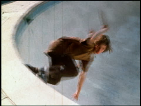 1970s medium shot tracking shot teenage boy with long hair skateboarding in drained swimming pool / friends watching in background - skateboardfahren stock-videos und b-roll-filmmaterial