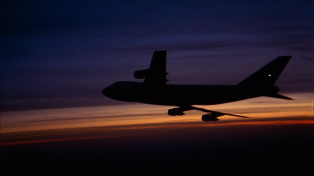 1970s medium shot zoom out silhouette of 747 airplane flying at dusk