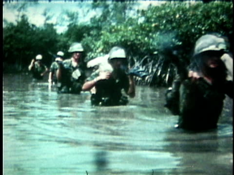1970s montage american soldiers on patrol wading across chest-high stream / vietnam - anno 1975 video stock e b–roll