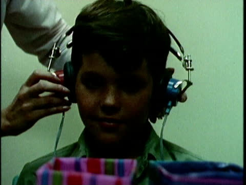 vidéos et rushes de 1970s montage boy undergoing hearing examination, los angeles, california, usa, audio - équipement