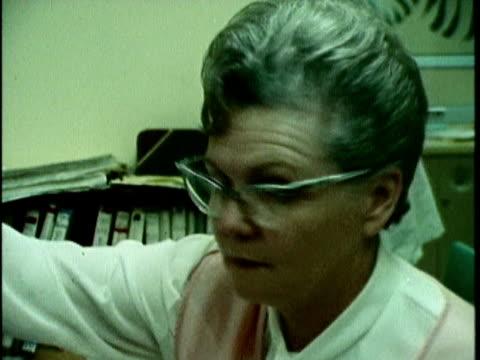 vídeos de stock, filmes e b-roll de 1970s montage hospital receptionist at work, los angeles, california, usa, audio - recepcionista