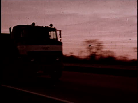 1970s MONTAGE Large trucks driving on the interstate / United States