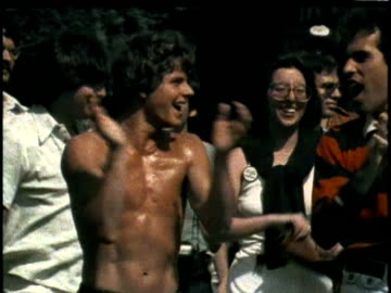 1970s montage los angeles gay pride parade / various shots of men and women marching in parade, clapping, holding raised hands / audio - diritti lgbtqi video stock e b–roll
