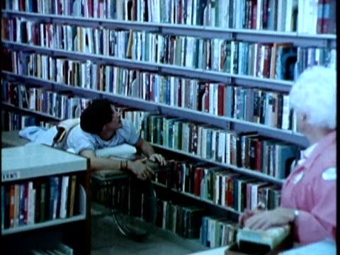 vidéos et rushes de 1970s montage nurse giving book to handicapped patient, los angeles, california, usa, audio - rayonnage de livre